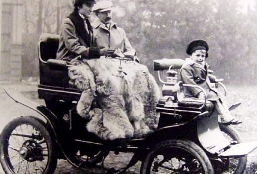 Black and white image of a family on a chariot during 1905-1920.