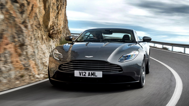 Aston Martin DB11 in grey driving on the road.