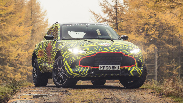 Aston Martin DBX parked in the forest with the lights on.