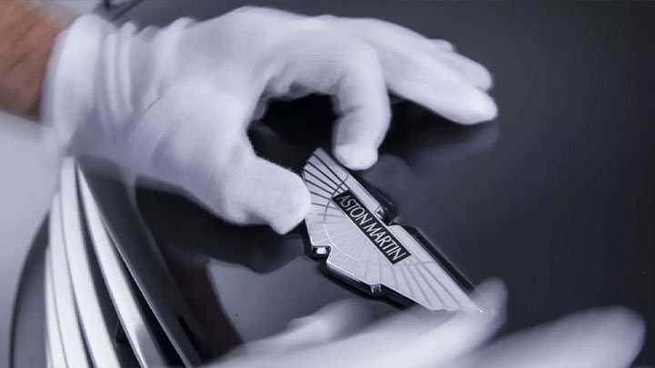 technician applying aston martin badge