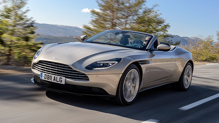 Pearl Blonde Aston Martin DB11 V8 Volante, driving with roof down