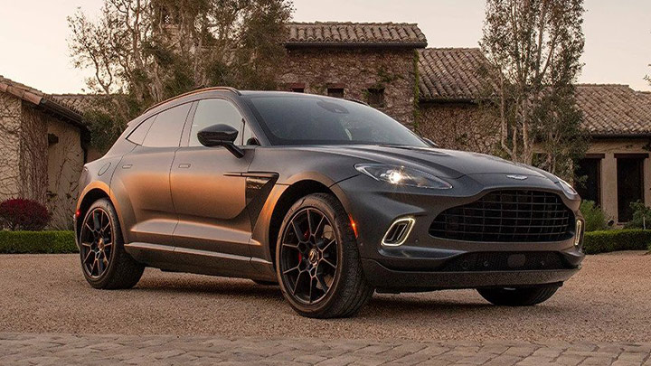 Black Aston Martin DBX, parked in country house yard