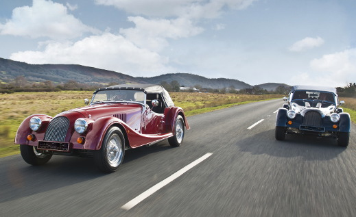 Two Morgan Plus 4s driving on the road.