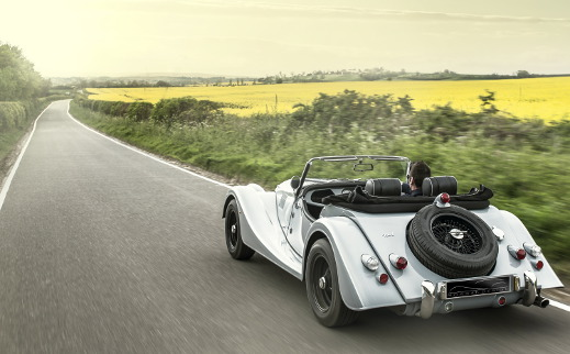 White Morgan Plus 4 driving on the road.