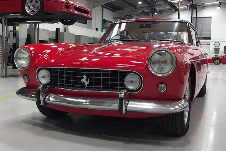 Red 1959 Ferrari 250 GTE in the workshop.