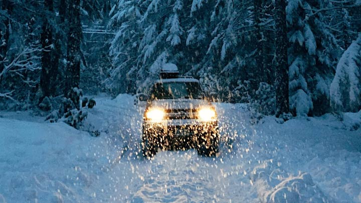 Car driving in the snow with headlights on