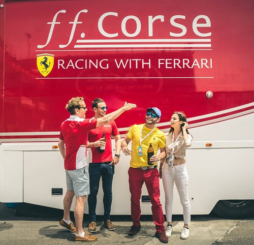 People stood in front of the racing with Ferrari bus.