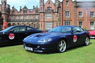 Blue Ferrari 550 Maranello parked on the grass.