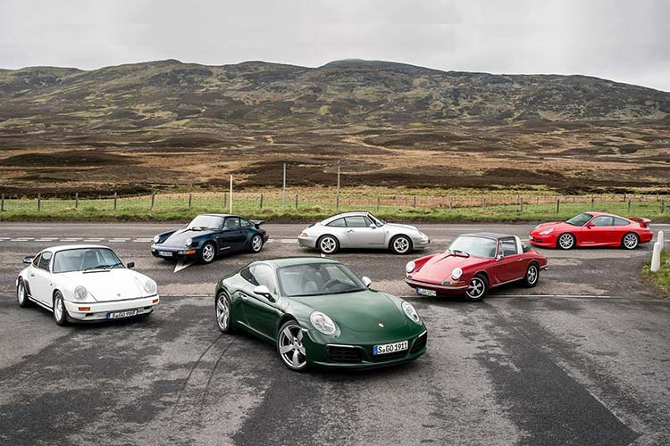 Group of Porsches parked on the road.