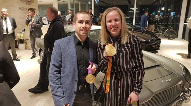 Lora and Neil Fachie stood in front of an Aston Martin holding their gold medals.