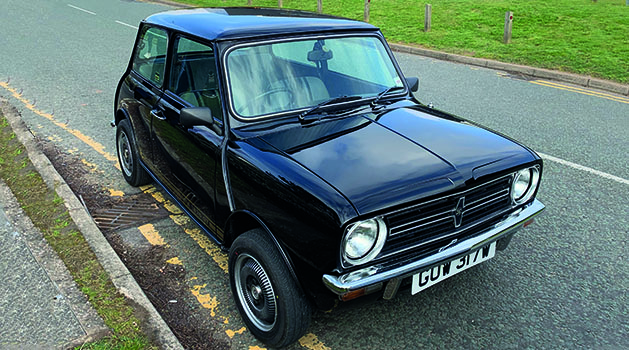 Black Austin Morris Mini 1275 GT parked on the side of the road.