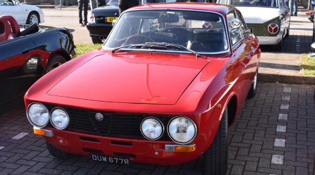 Red Alfa Romeo 1600 GT Junior in Pendragon PLC car park for Car Cafe.