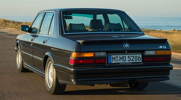 Black BMW 'E28' M5 (1985) driving by the sea.