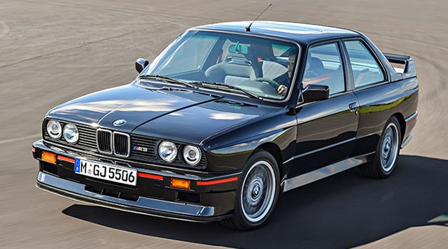 Black BMW 'E30' M3 (1986) driving on a track.