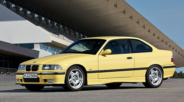 Yellow BMW 'E36' M3 (1992) parked up.