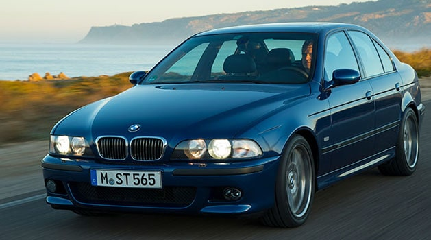 Blue BMW 'E39' M5 (1998) driving by the sea.