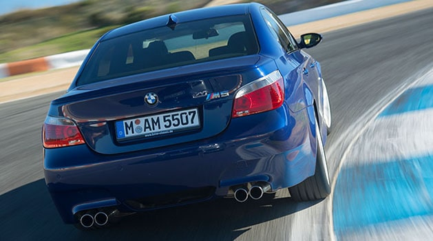 Blue BMW 'E60' M5 (2005) driving on a track.