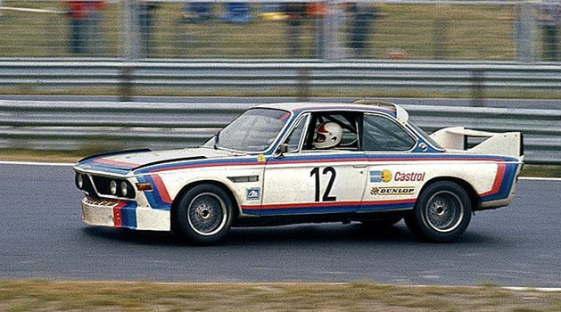 White BMW 3.0 CSL driving on the track.