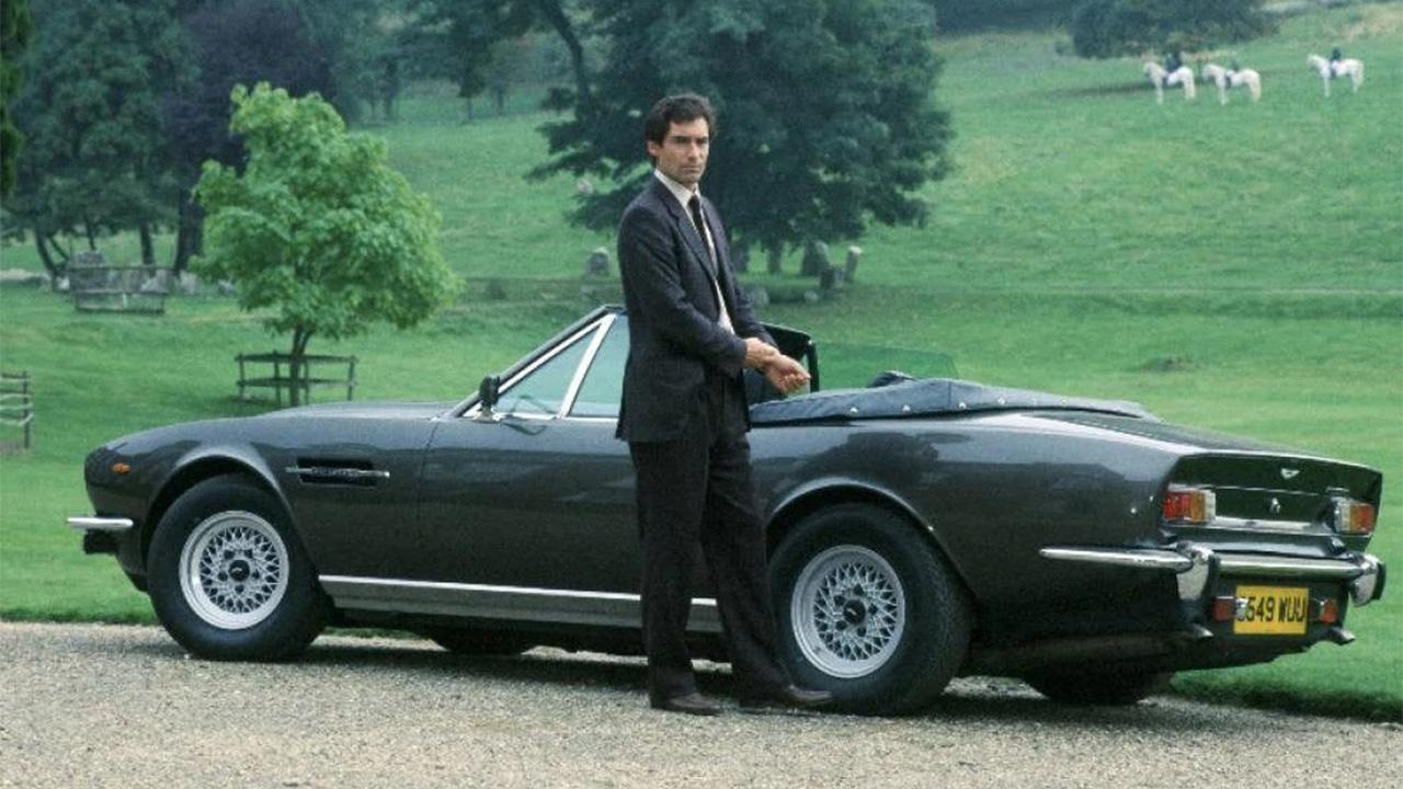 Timothy Dalton standing next to an Aston Martin Vantage Convertible