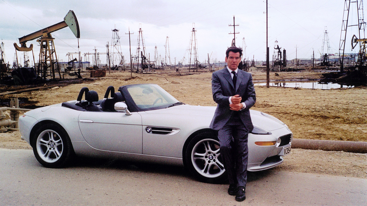 Pierce Brosnan leaning on a silver BMW Z8 with the roof down