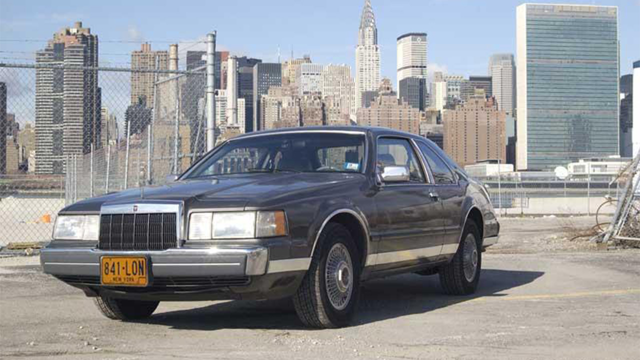 Lincoln Continental parked in front of city backdrop