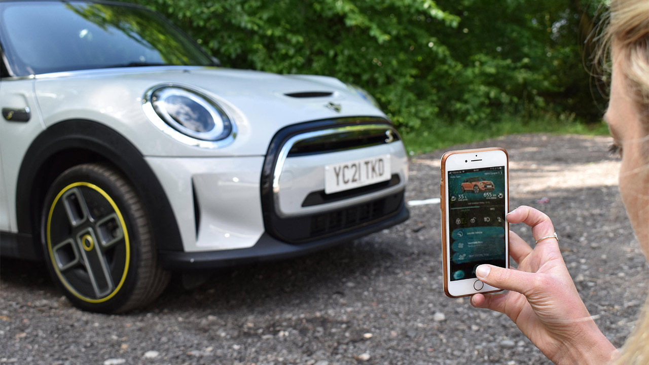Woman using MINI Connected smartphone app, MINI Electric parked in background