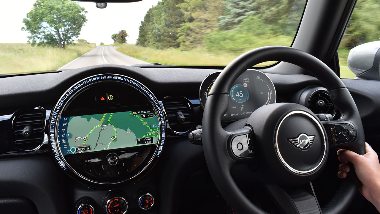 MINI Electric being driven down country road with satellite navigation on