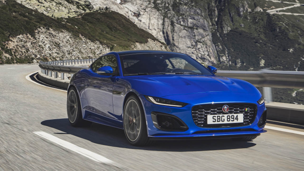 blue jaguar f-type driving in mountains