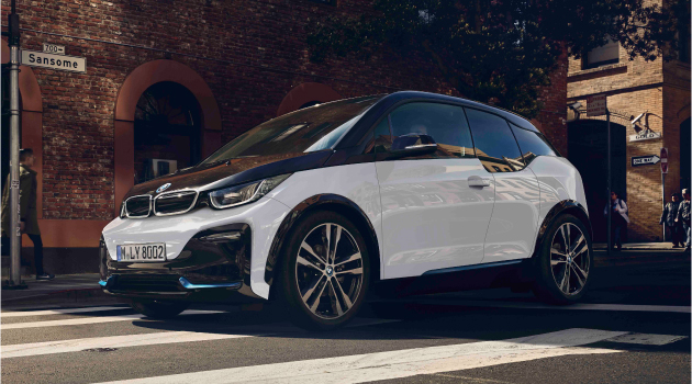 White and black BMW i3 All-Electric driving on the road.