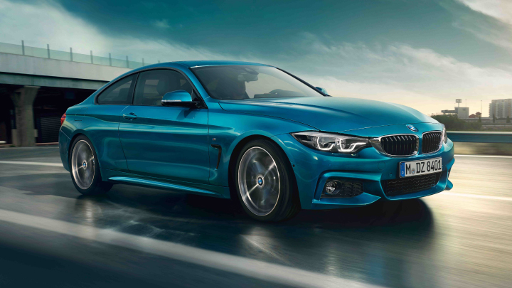 BMW 4 Series Coupe in blue driving on the road.