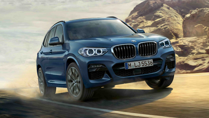 BMW X3 in blue driving on the road.
