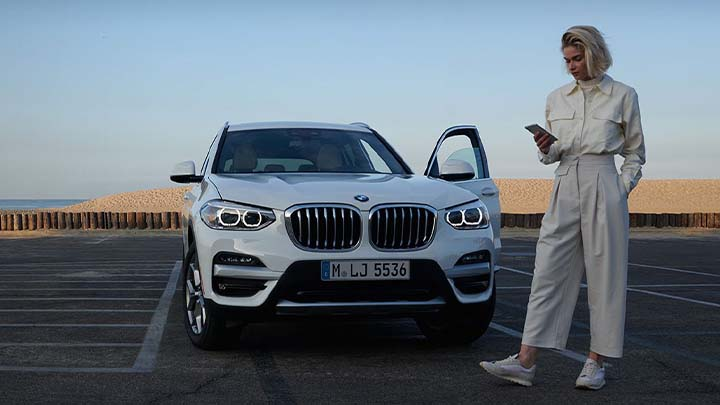 woman standing in front of bmw x1 using my bmw app