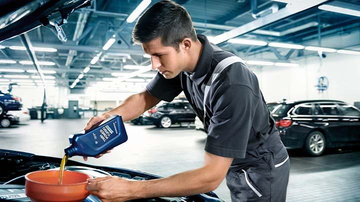 bmw technician replacing engine oil