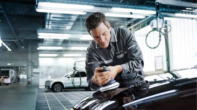 BMW Vehicle Technician looking at vehicle aftersales.