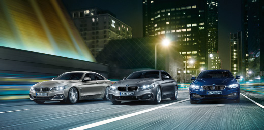 Three BMW's driving on the road at night.