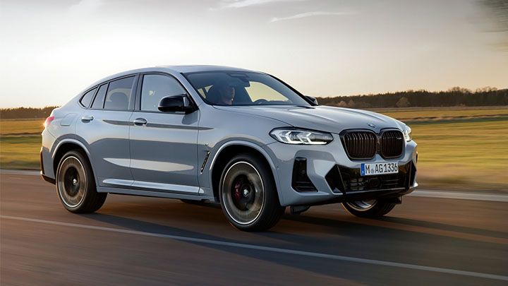 Silver BMW X4, driving in sunset
