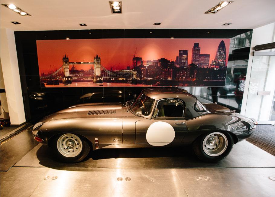 Jaguar Lightweight E-Type parked over the showroom elevator.