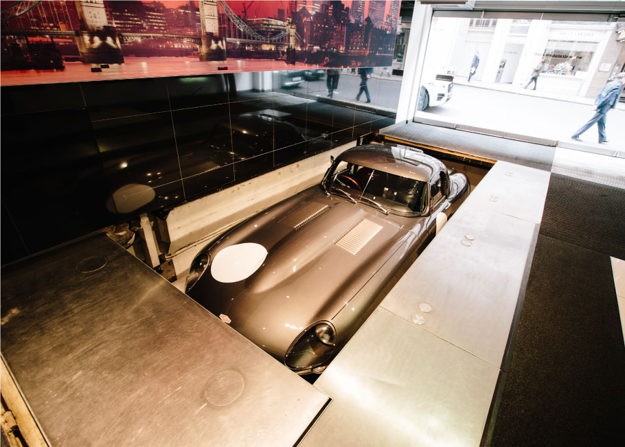 Lightweight E-Type goes down the elevator in the Mayfair showroom.