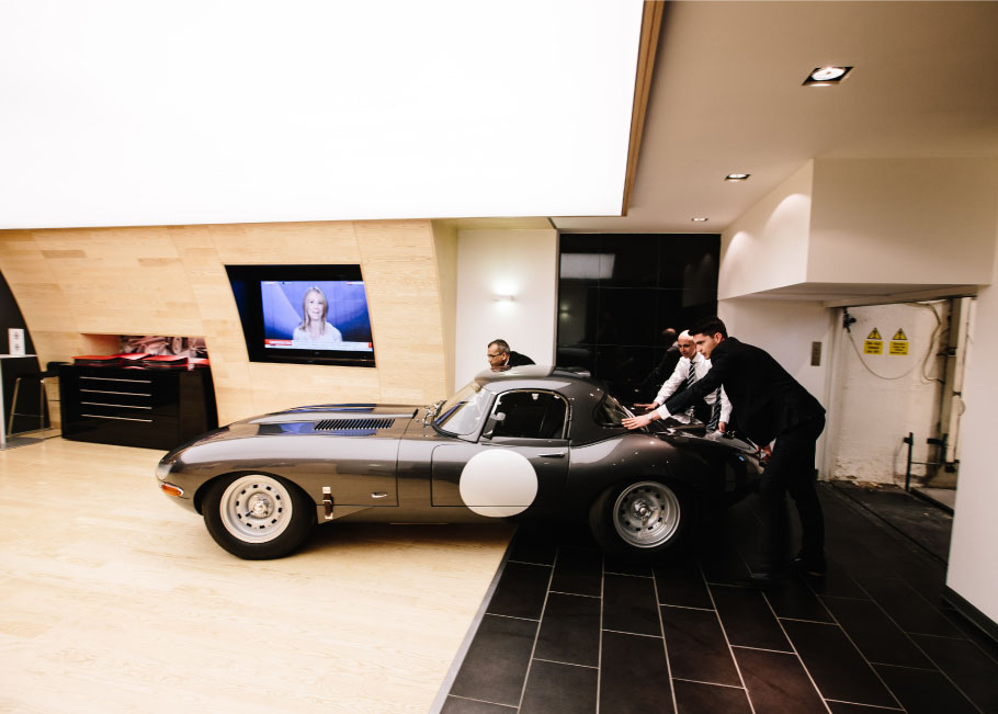 Staff pushing the Jaguar Lightweight E-Type in the basement.