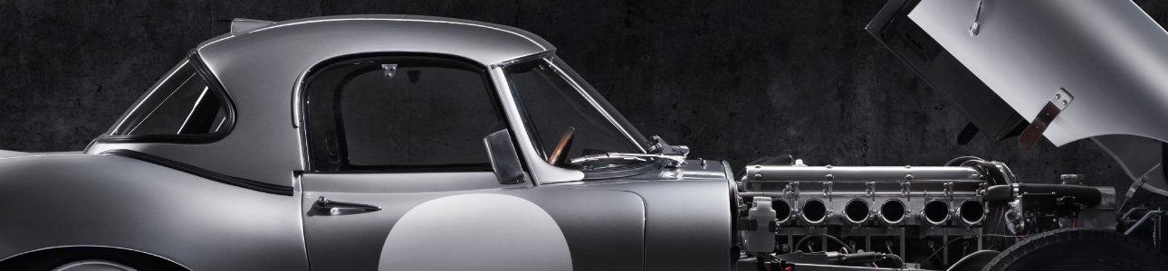 E-Type with the bonnet open showing the engine.