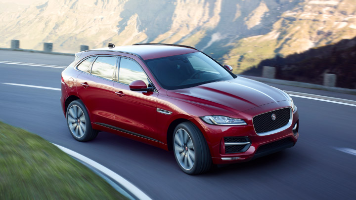 Red Jaguar F Pace driving on the road.