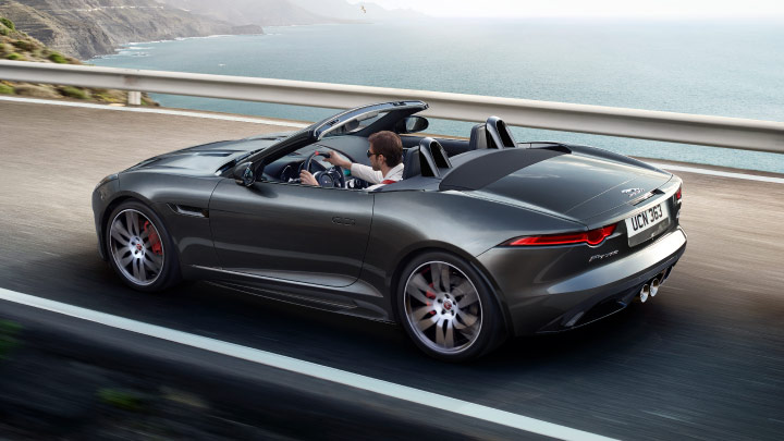 Grey Jaguar F Type driving on the road.