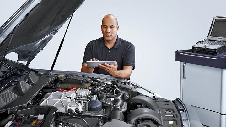 technician inspecting jaguar engine bay