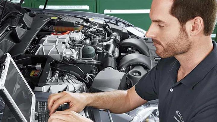 jaguar technician completing diagnostics on an engine