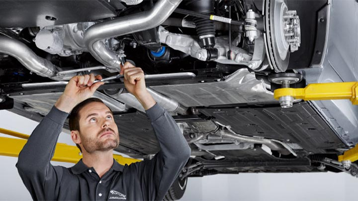 technician completing repair on exhaust system of jaguar