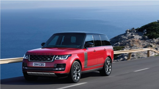 Red Range Rover driving by the coast.