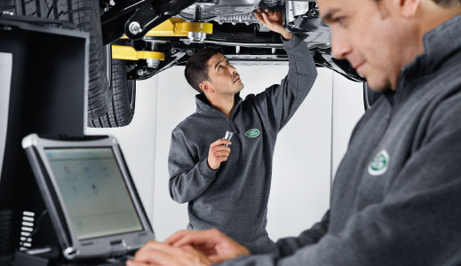 Land Rover technicians servicing a car.