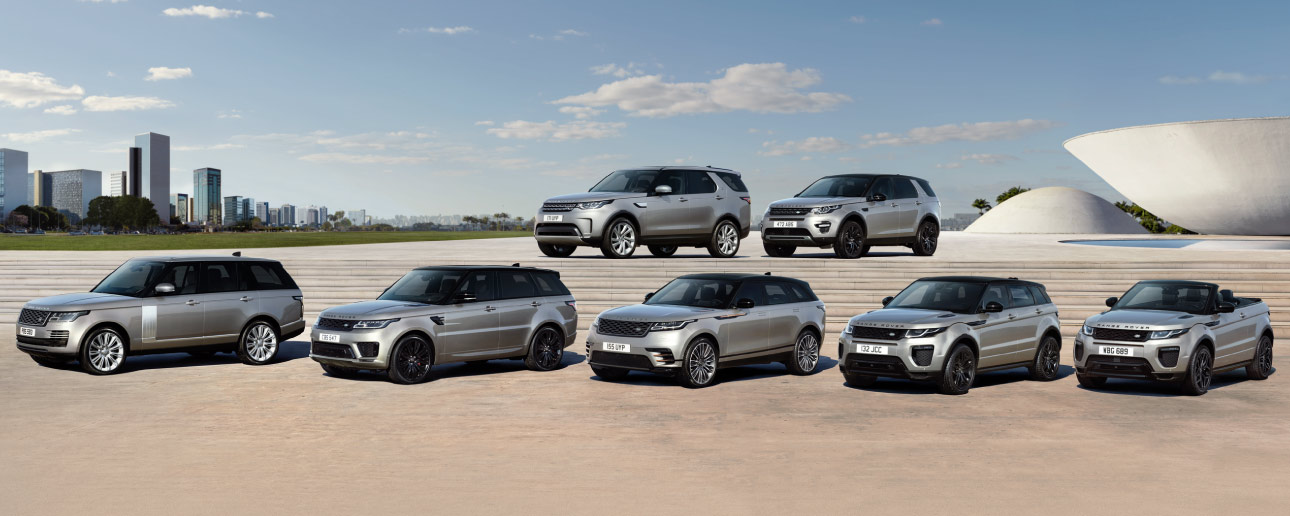 Seven Land Rovers parked.