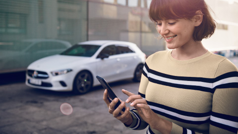 Mercedes-Benz owner booking service via smartphone, a-class parked in background
