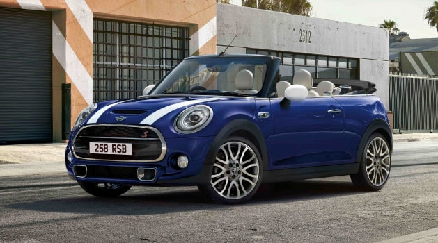 Blue MINI Convertible with the roof down parked on the side of the road.
